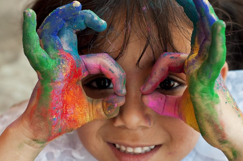 Little girl with colourful paint on her hands, making a face and smiling.