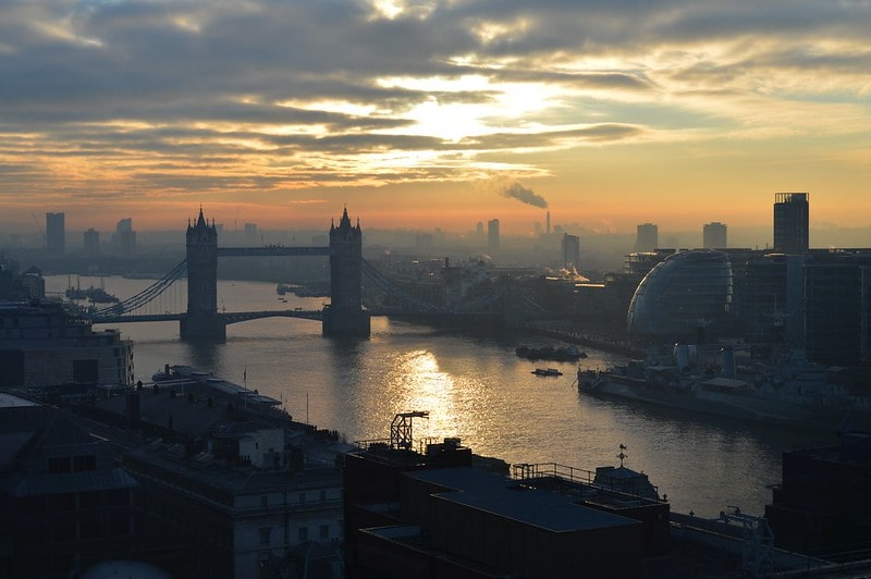 View of Tower Bridge and the Thames riverbank at dawn.