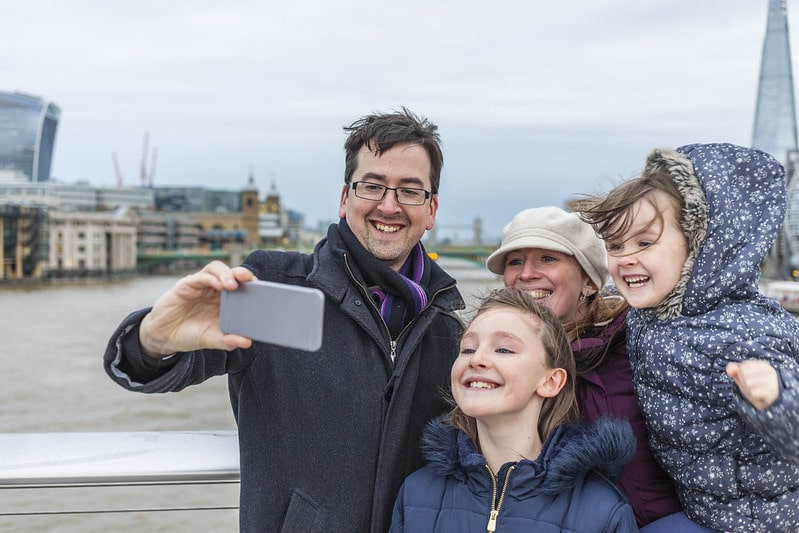 Family taking a selfie by the Thames river with London monuments in the background.