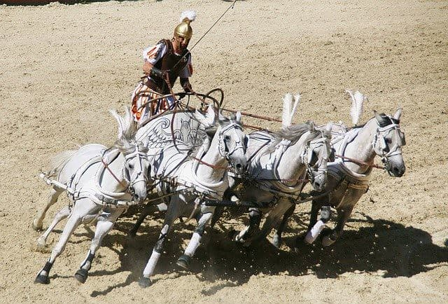 Roman chariot racer driving his chariot around the sand track led by four white horses.