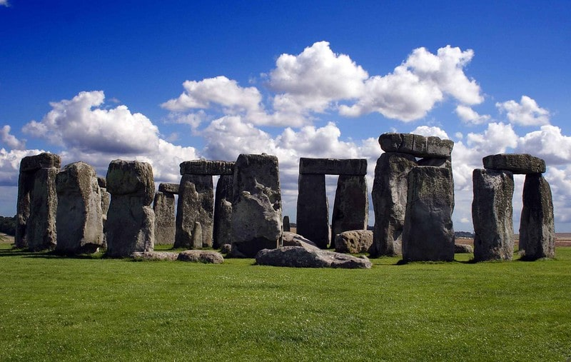 Stonehenge on a sunny day with a blue sky and clouds.