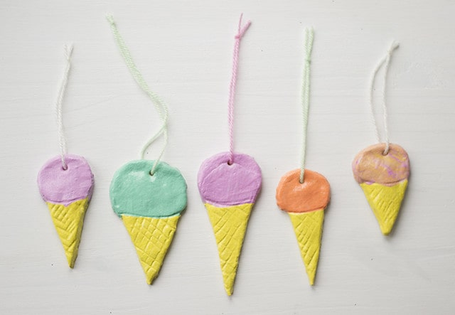 Ice cream cones made from salt dough with a string tied through the top for hanging.