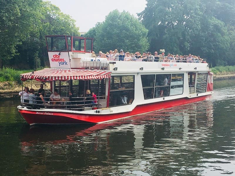 A City Cruises York boat with passengers in the enclosed saloon and the upper deck.