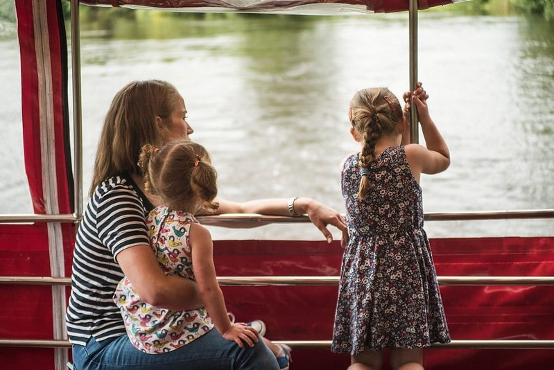 A mother and her two children admiring the view from a City Cruises boat.