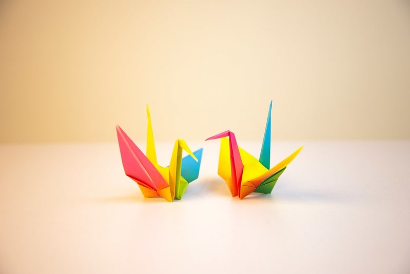 Two multi-coloured origami birds on the tabletop.