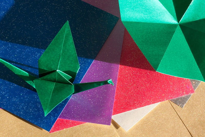 Different coloured sheets of paper with origami animals made out of some of them.
