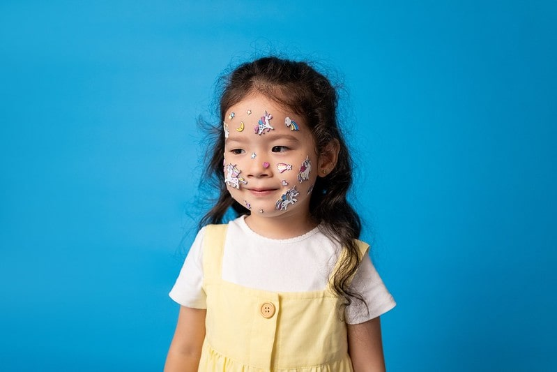 Little girl with unicorn stickers stuck on her face, standing in front of a blue background.