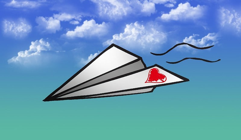 Cartoon origami plane, with a heart drawn on one flap, flying through the sky.