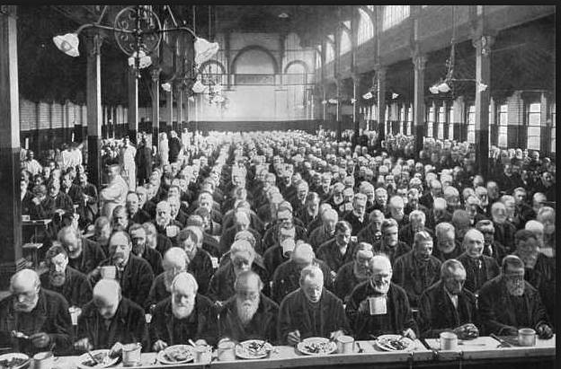 Rows and row of men in a black and white photograph of a Victorian workhouse.