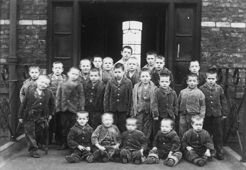 Black and white photo of children standing in front of the Victorian workhouse.