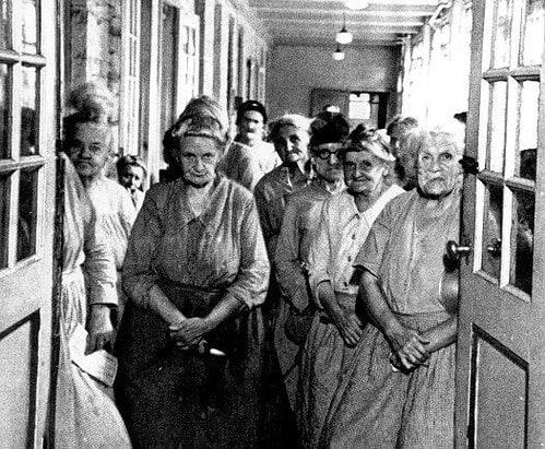 Women standing in the hallway of the Victorian workhouse.