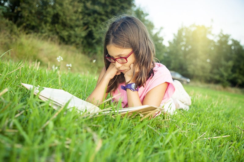 Young girl lying on her stomach in the grass reading a book of Victorian poetry.