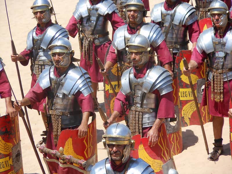 Group of men in Roman soldier armour marching.