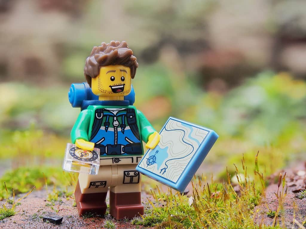 A Lego explorer holding a lego map and compass.