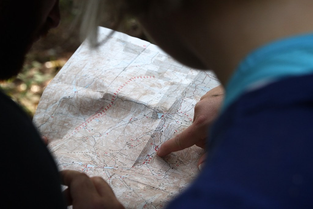 Child holding open a map, reading it and pointing to a location.
