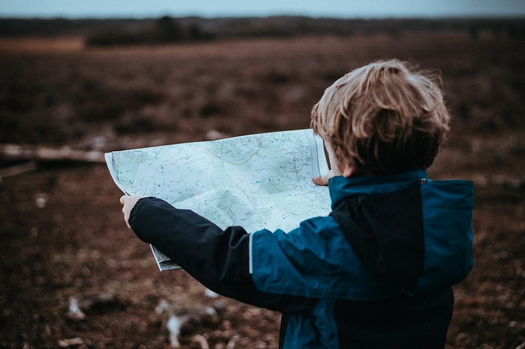 Young boy holding up a map reading it in the countryside.