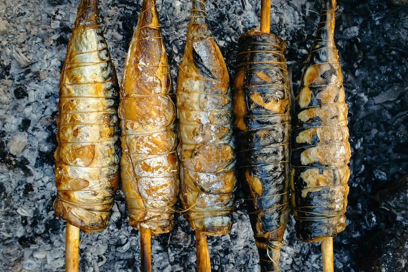 Spit-roasted fish on the embers of the coal.