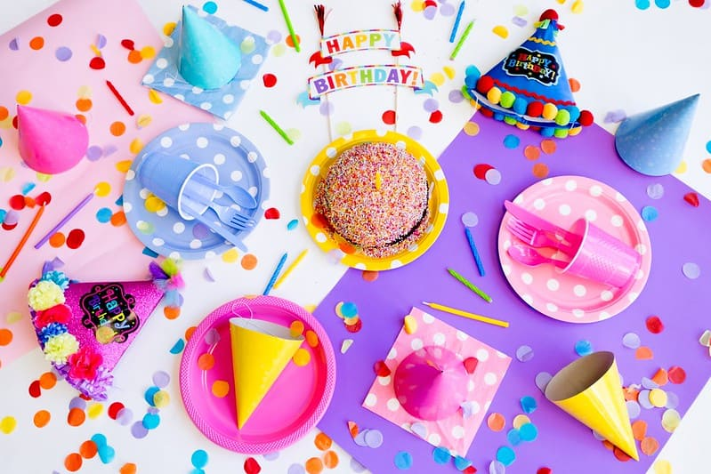 Table with a birthday cake covered in sprinkles, paper plates and party hats and colourful birthday decorations on it.