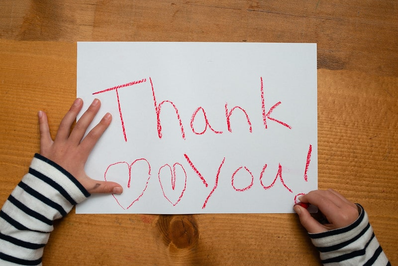 Child has written 'thank you' in red crayon on a piece of paper.