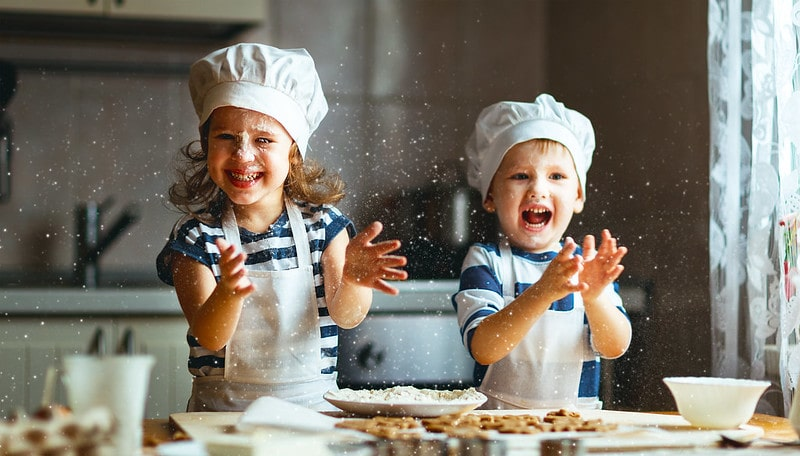 Two kids in the kitchen, wearing chef's hats and aprons, baking and getting flour everywhere.