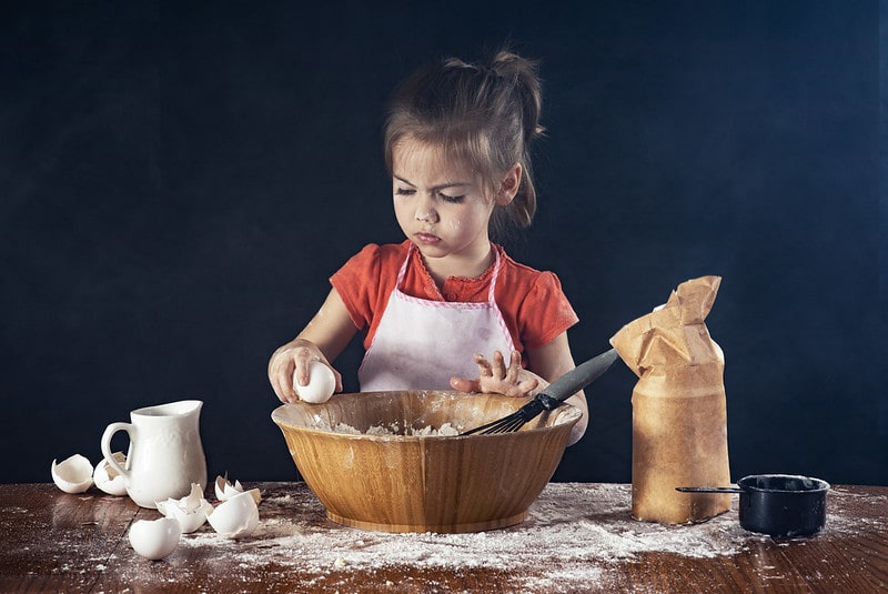 Little girl wearing a pink apron baking a cake, breaking an egg into the bowl.