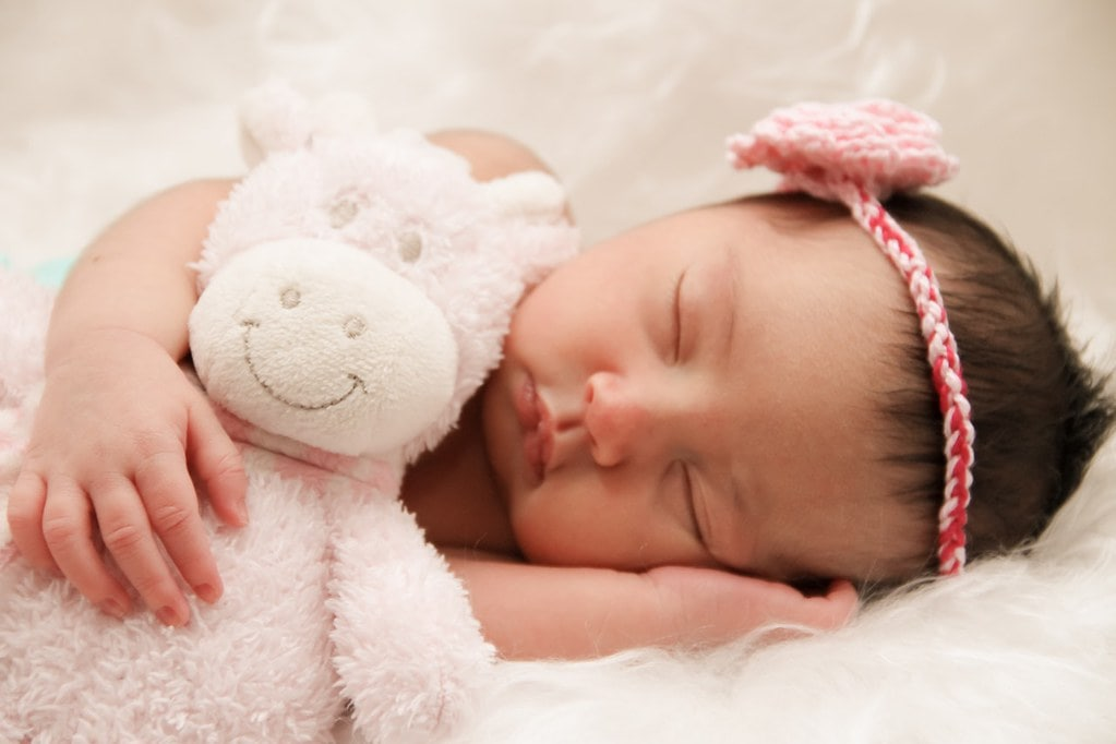Baby girl lying on her side sleeping, holding a pink teddy in her arms.