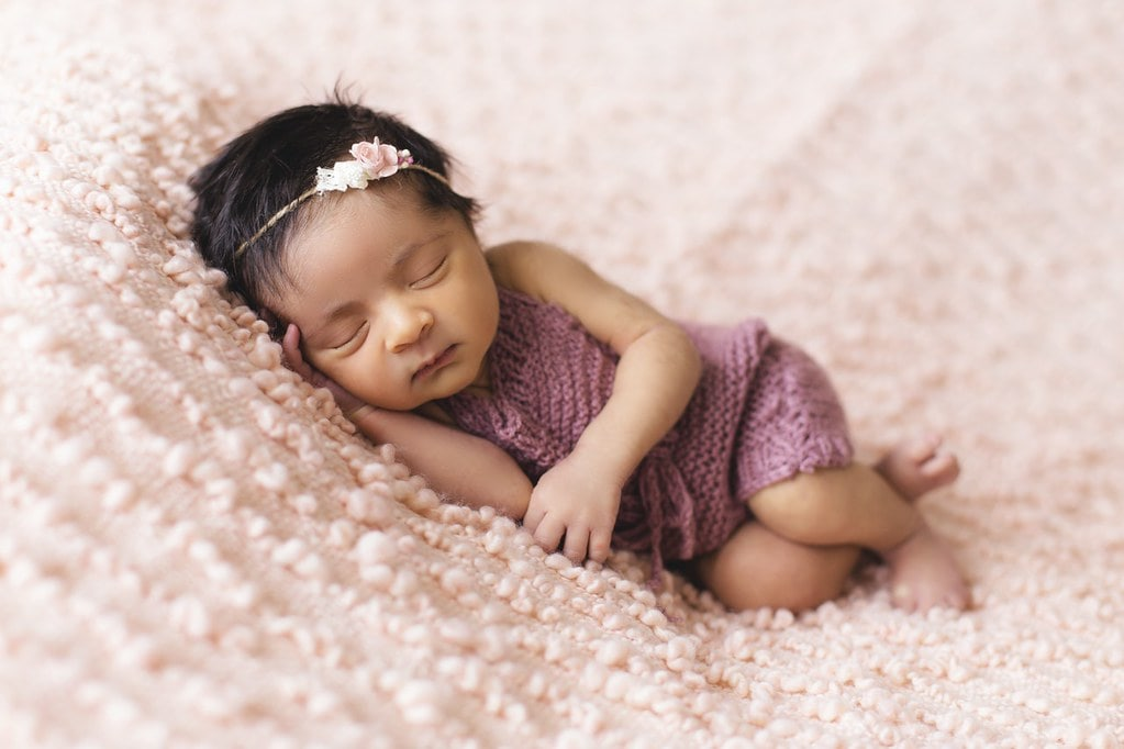 Baby girl wearing a flower hairband, sleeping on a pink blanket.