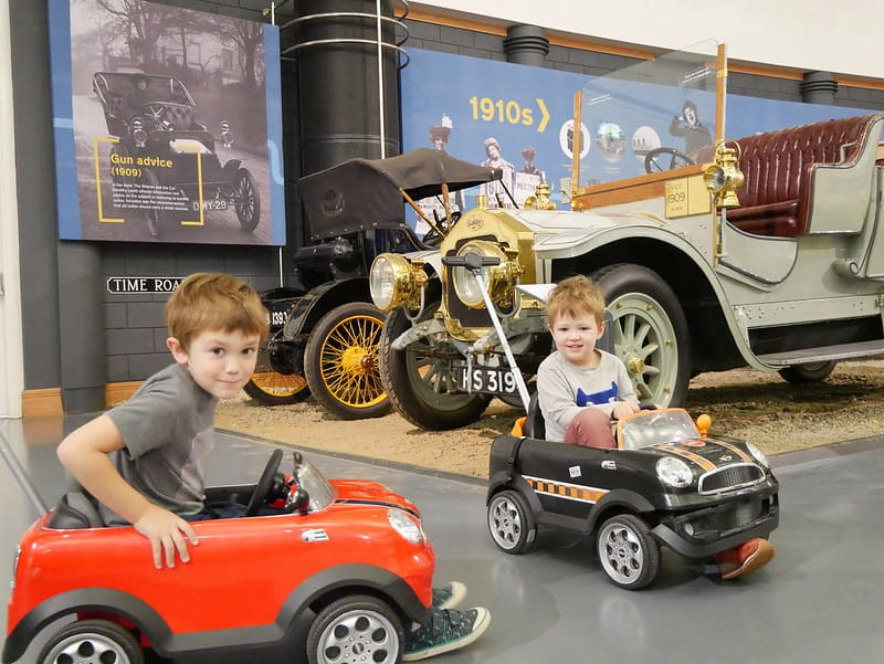Two children playing in toy cars at the British Motor Museum.