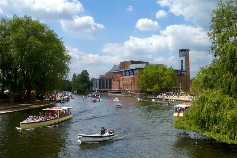 The River Avon with several boats cruising down it and the Royal Shakespeare Theatre located on the banks.