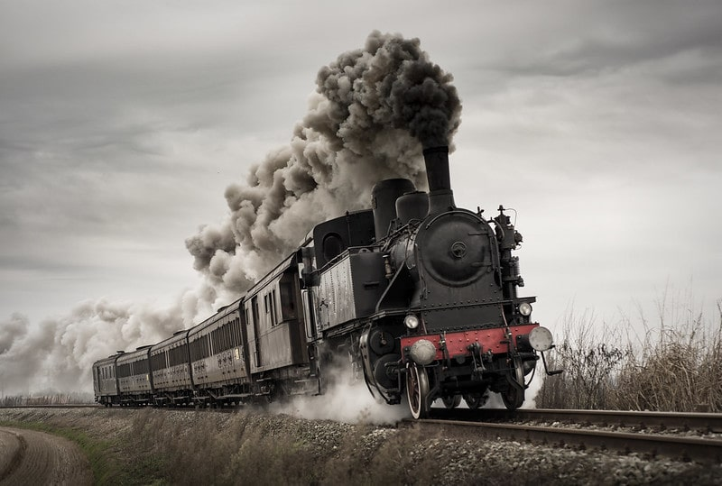 A Victorian steam train moving along the railways, producing black steam as it goes.