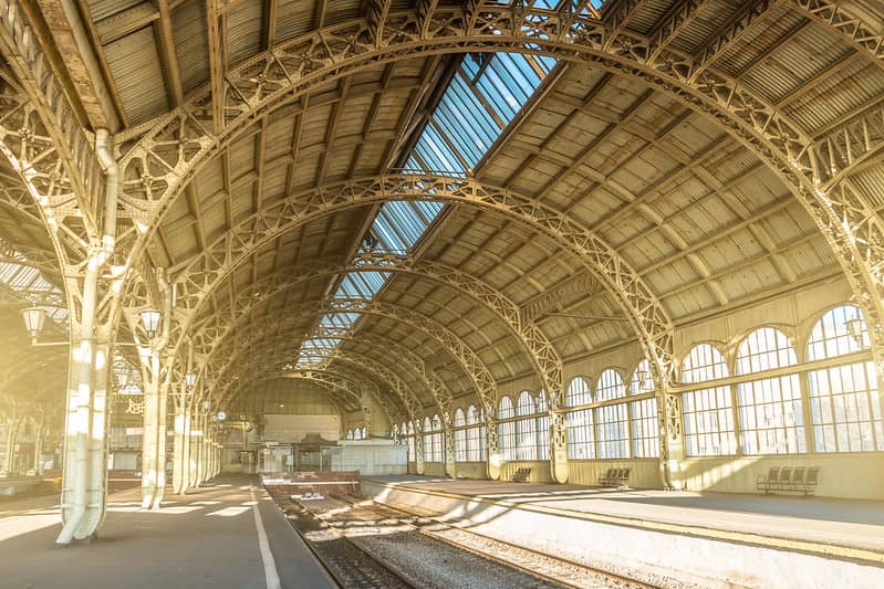 The platforms and tracks of an empty train station with an arched roof.