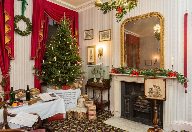 A Victorian style living room with Christmas decorations adorning the room.