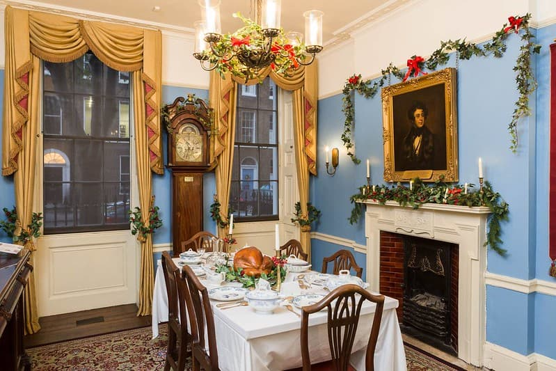 A Victorian dining room adorned with Christmas decorations and a feast, including roast turkey, on the table.
