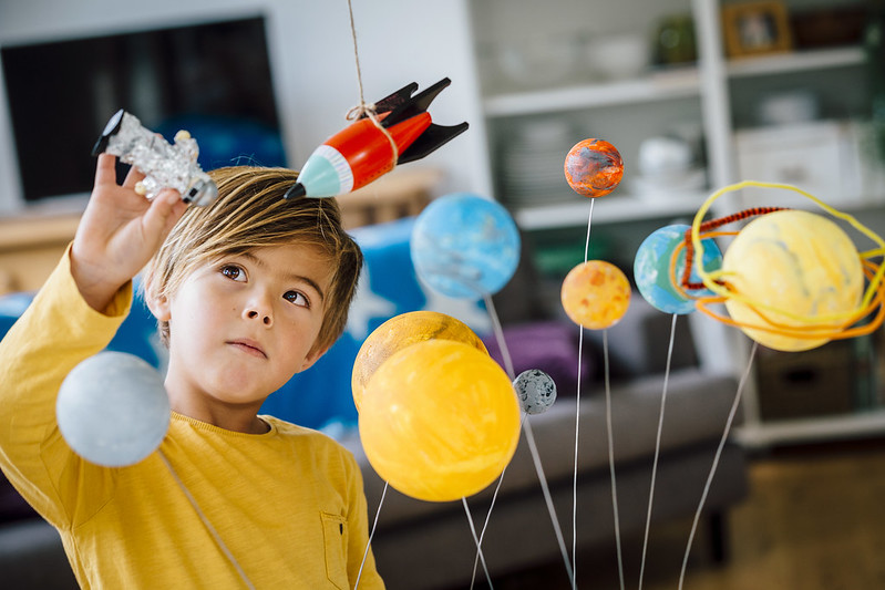 Little boy playing with his homemade planetarium as he holds an astronaut