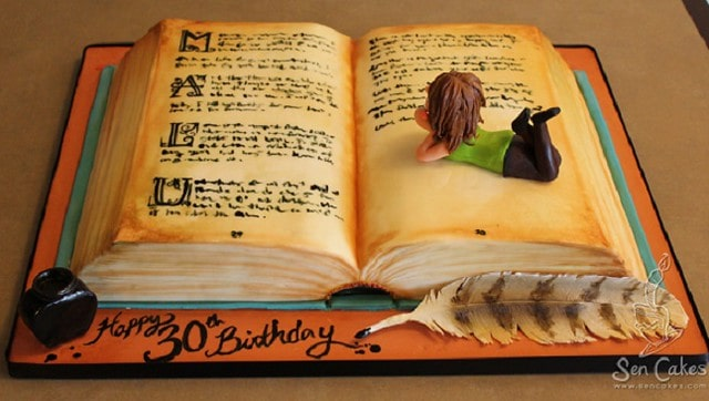 A book cake, pages open and a person figurine lying on the pages.