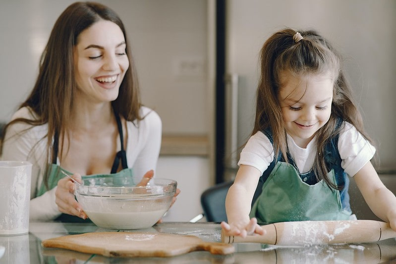 Happy mum and daughter in the kitchen baking a cake.