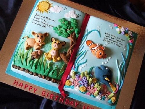 Book cake decorated with a scene from The Lion King on one page and from Finding Nemo on the other.