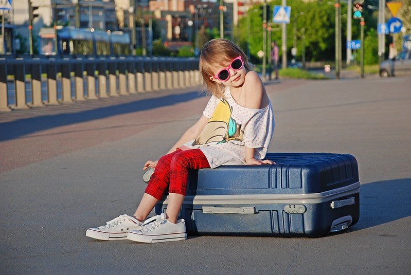 Young girl sitting on a suitcase wearing sunglasses and posing on holiday.