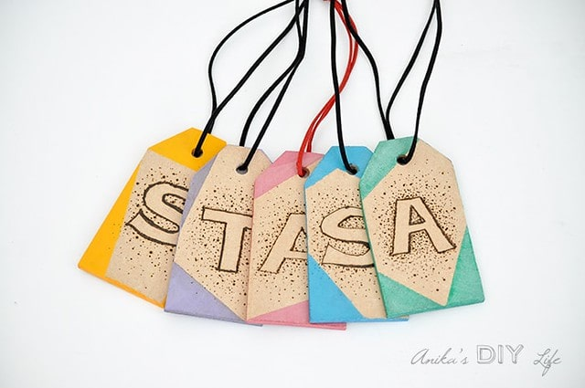 DIY wooden luggage tags, decorated with letters drawn on them.