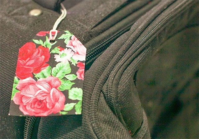 Paper DIY luggage tag in a floral print, tied onto a suicase.