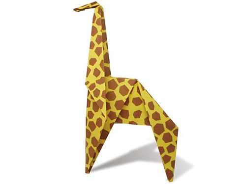 An origami giraffe made from a patterned piece of yellow paper.