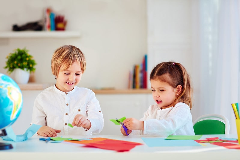 Little boy and girl sat at the table making origami giraffes.