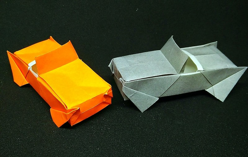 Two origami cars, one orange and one grey, on a black surface.