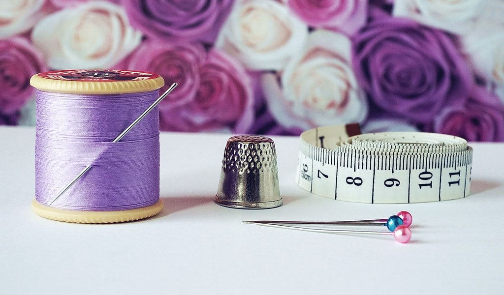 Sewing equipment: lilac thread, a needle, thimble and measuring tape.