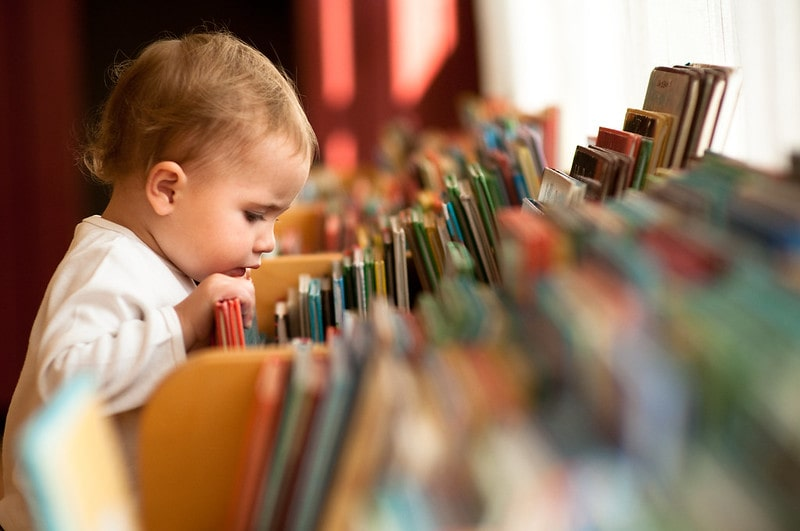 Toddler flicking through books in the library.