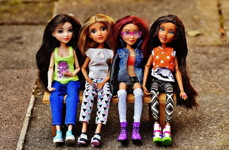 Four Barbie dolls wearing chic outfits sat on a bench together.
