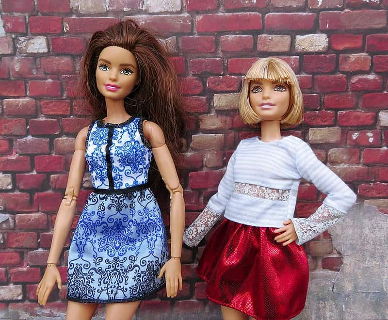 Two Barbie dolls striking a pose in front of a red brick wall.