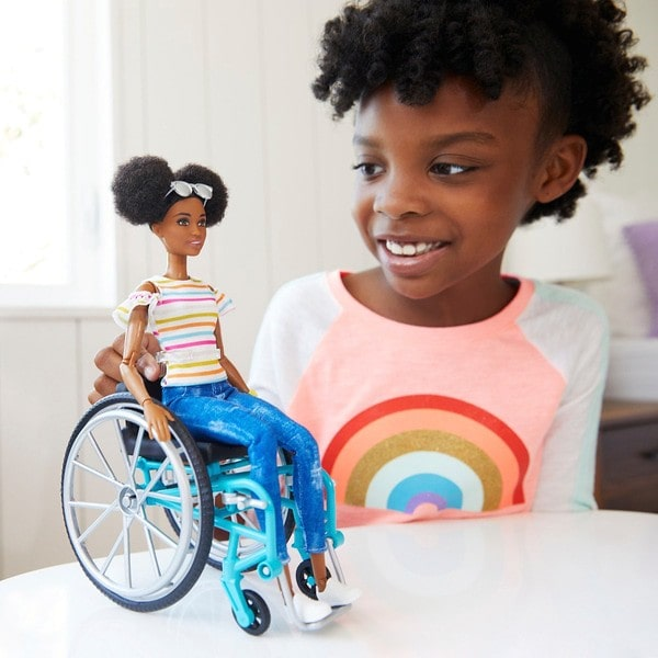 Young girl playing with her Barbie fashionista doll in a wheelchair.
