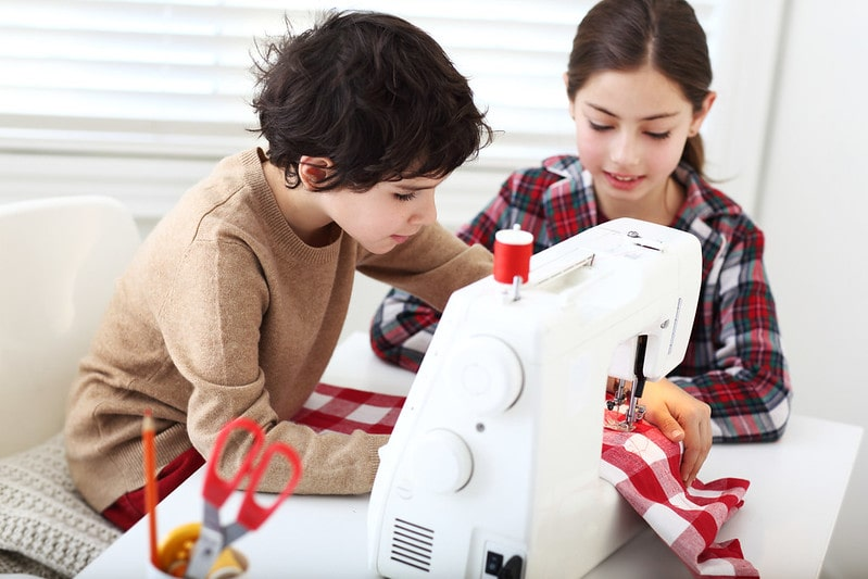 Two children using a sewing machine together.