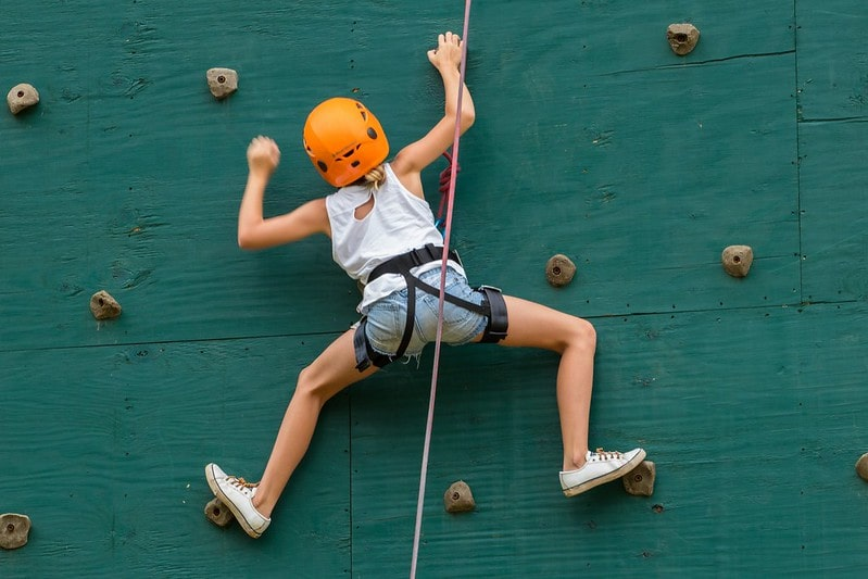 Girl in an orange helmet climbing up a green rock wall.